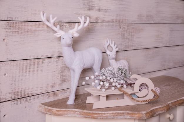 Jeleń, sanki, sanki jako dekoracja domu. boże narodzenie i nowy rok wystrój domu. wnętrze pastelowe kolory, styl vintage na drewnianym