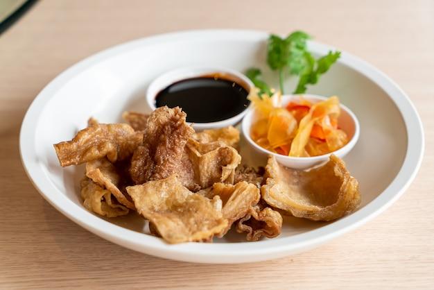 Jelita wieprzowe smażone w głębokim tłuszczu ze słodkim czarnym sosem - azjatyckie jedzenie