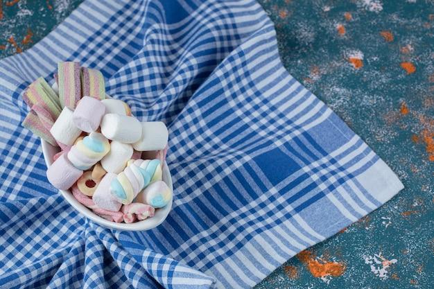 Jellybeans i marshmallows na białym talerzu ceramicznym.