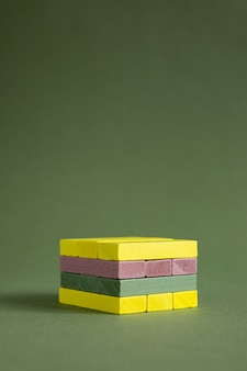 Jenga drewno kolorowe zielone i żółte na zielonym tle kopia przestrzeń platformy dla produktu