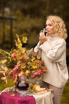 Jesień. dziewczyna pije gorącą owocową czerwoną herbatę w filiżankach. stół ustawiony na brzegu jeziora ozdobiony jest bukietem jesiennych liści. herbaty owocowe do picia z cytryną, jabłkami