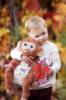 Jesień emocjonalny portret dziewczynki. całkiem mała dziewczynka z małpą zabawką w jesiennym parku. jesienne zajęcia dla dzieci. halloween i święto dziękczynienia zabawa dla rodziny.