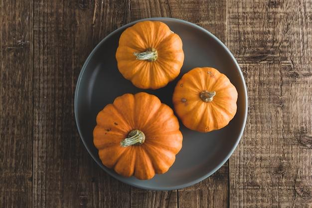 Jesień, jesień dziękczynienia z pomarańczową dynią w talerzu na rustykalnym drewnie