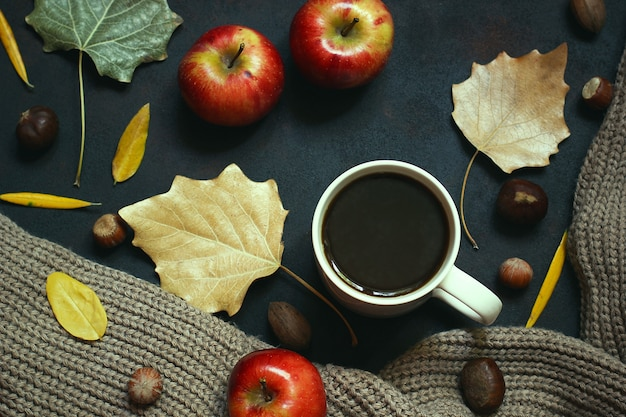 Jesień, jesienne liście, gorąca parująca filiżanka kawy i ciepły szalik lub kardigan. sezonowa, poranna kawa, niedzielny relaks i martwa natura.