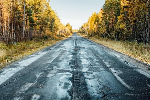 Jesień krajobraz z drogą uszkodzonym asfaltem, drzewami i niebem