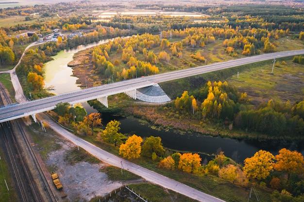 Jesień krajobraz z rzeką i mostem. drzewa pomarańczowe.