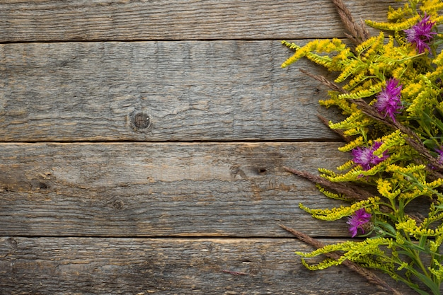 Jesień kwiaty na drewnianym nieociosanym tle. skopiuj miejsce