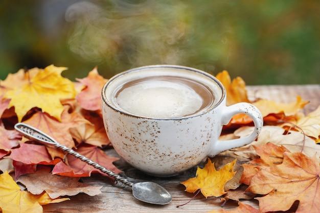 Jesień, liście jesieni, gorąca parująca filiżanka kawy.