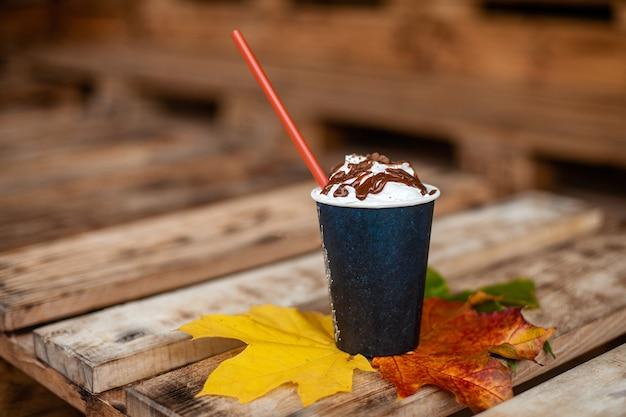 Jesień, liście jesienią, gorąca parująca filiżanka kawy na drewnianym stole