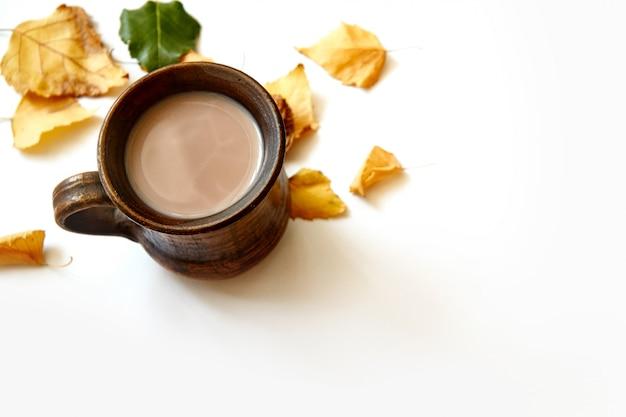 Jesień liście z kawową lub herbacianą filiżanką na bielu