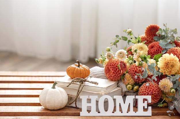 Jesień martwa natura z bukietem kwiatów chryzantemy, ozdobne słowo do domu i dynie na rozmytym tle.