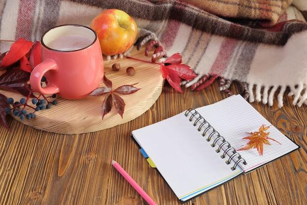 Jesień martwa natura z filiżanką kakao, notebookiem i jabłkiem.