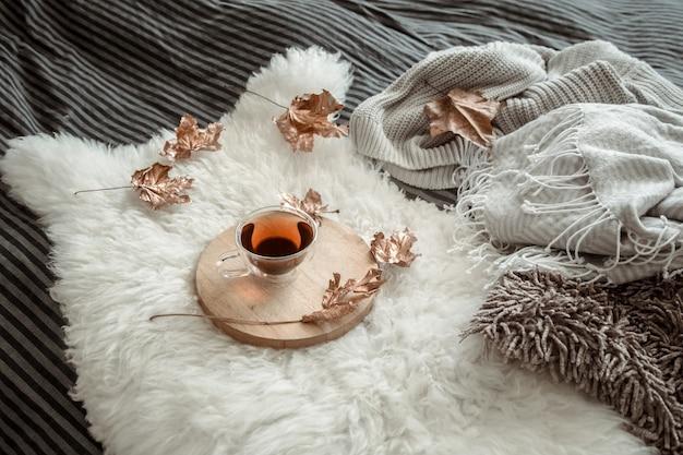 Jesień martwa natura z liśćmi i filiżanką herbaty.