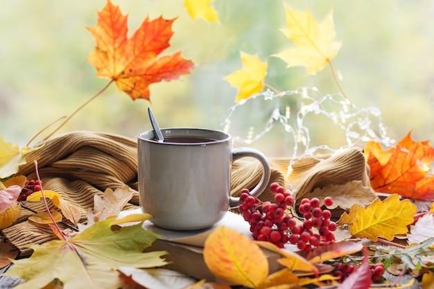 Jesień martwa natura z pięknym bokeh. jesienne liście i filiżanka gorącej parującej kawy lub herbaty, dynie i jesienne zbiory. sezonowa, poranna kawa, niedzielny odpoczynek i koncepcja martwej natury