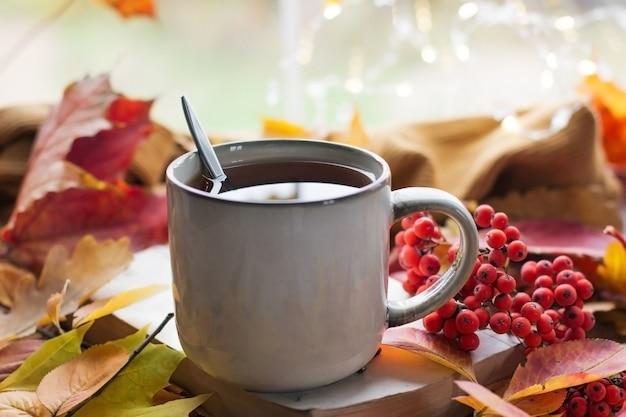 Jesień martwa natura z pięknym bokeh. jesienne liście i filiżanka gorącej parującej kawy lub herbaty, pomarańczowe dynie i jesienne zbiory. sezonowa, poranna kawa, koncepcja martwej natury, makieta układu
