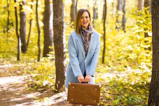 Jesień, moda, koncepcja ludzi - kobieta z brązową walizką retro spacerując po jesiennym parku