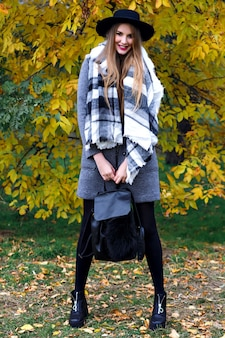 Jesień moda portret eleganckiej kobiety glamour pozuje w niesamowitym parku miejskim, stylowy płaszcz, plecak i vintage kapelusz. samotny spacer, zimna pogoda