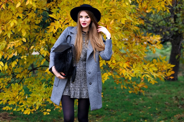 Jesień moda portret eleganckiej kobiety glamour pozuje w niesamowitym parku miejskim, stylowy płaszcz, plecak i vintage kapelusz.
