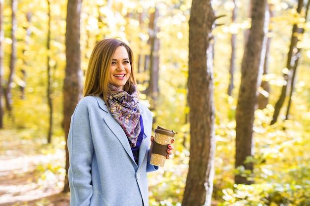 Jesień, natura, koncepcja ludzi - młoda brunetka kobieta w niebieskim płaszczu stojąca w parku przy filiżance