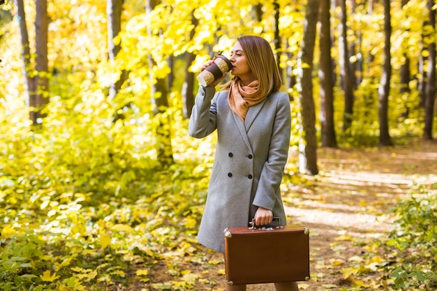Jesień, natura, koncepcja ludzi - młoda brunetka pije kawę w parku jesień