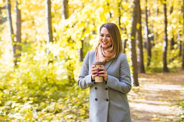 Jesień, natura, koncepcja ludzi - młoda kobieta w niebieskim płaszczu stojąca w parku na tle