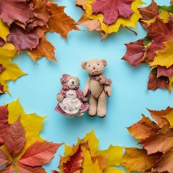 Jesień niebieski powierzchni z zabawkami nosi w ramce z liści