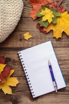 Jesień obrazek z notatnikiem, piórem, kolorów żółtych liśćmi i szalikiem na drewnianym tle ,.