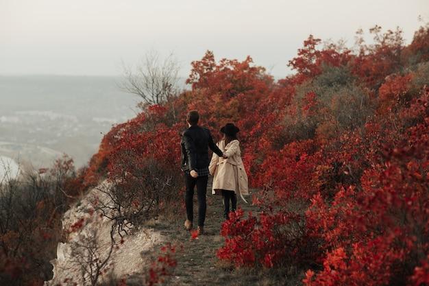 Jesień piękna młoda para w stylowych ubraniach idzie na wzgórze i trzyma się za ręce