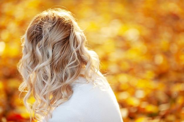 Jesień portret blondynka na zewnątrz z kręconymi włosami. widok z tyłu. skopiuj miejsce