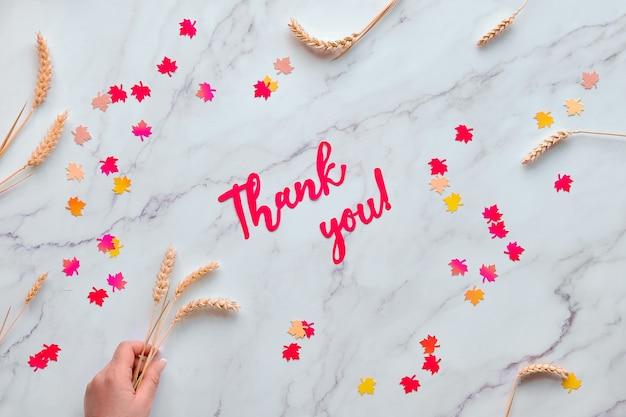 Jesień sezonowe tło z kłosami pszenicy i konfetti w kształcie czerwonych i żółtych jesiennych liści klonu. tekst na papierze dziękuję.