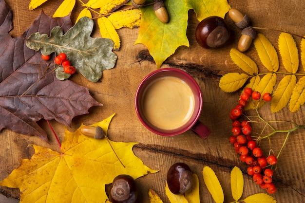 Jesień, spadków liście, gorąca parująca filiżanka kawy na drewnianym stołowym niedziela rano kawowy relaksujący i wciąż życia pojęciu. widok z góry.