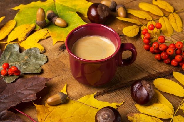 Jesień, spadków liście, gorąca parująca filiżanka kawy na drewnianym stołowym niedziela rano kawowy relaksujący i wciąż życia pojęciu.