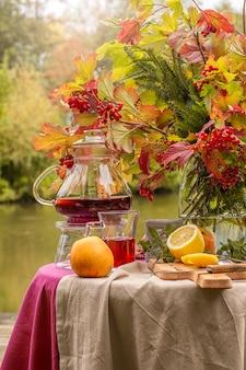 Jesień. stół ustawiony nad brzegiem jeziora ozdobiony bukietem jesiennych liści. spotkanie przy herbacie. herbaty owocowe z cytryną, jabłkami.