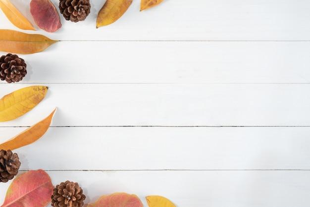 Jesień suszący liście na białym drewnie