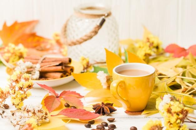 Jesień sztandar z filiżanką kawy z cynamonem na białym drewnie