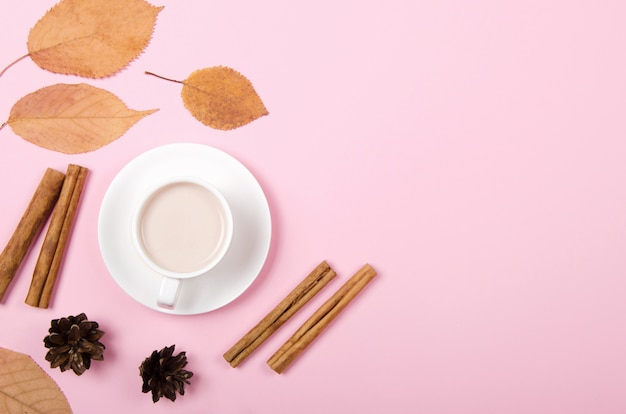 Jesień tło z kawą, cynamonem i liśćmi na jasnym tle