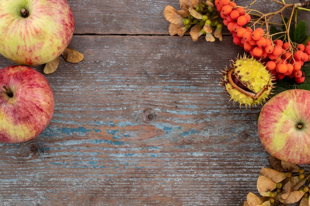 Jesień tło z opadłych liści i owoców z rocznika nakrycie na starym drewnianym stole. koncepcja święto dziękczynienia.