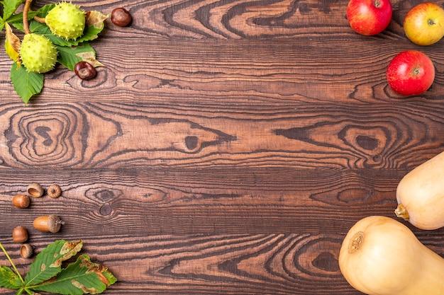 Jesień tło z orzechami i kasztanem, jabłkiem i dynią.