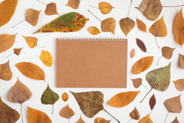 Jesień układ z zwiędłymi liśćmi i notatnikiem