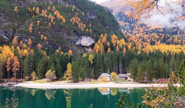 Jesień w lago di braies w tyrolu odbicie gór alp i kaplica w jeziorze włochy