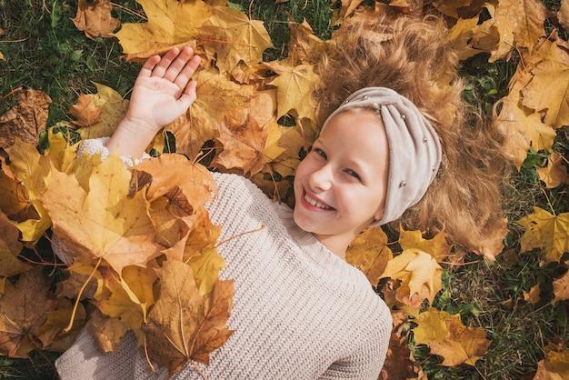Jesień zewnątrz portret dziecka dziewczyna spaceru w parku lub lesie w ciepły sweter z dzianiny.
