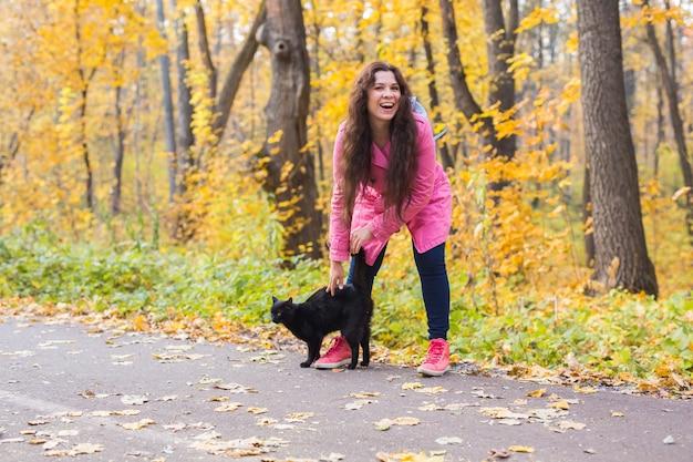 Jesień, zwierzęta, koncepcja ludzi - szczęśliwa kobieta śmiejąca się z czarnym kotem