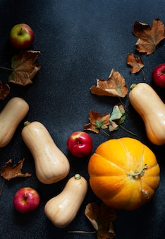 Jesieni dyniowy tło, różnorodne banie i żółci liście. święto dziękczynienia i halloween. kompozycja płasko-martwa. czarne tło, widok z góry. miejsce na tekst.