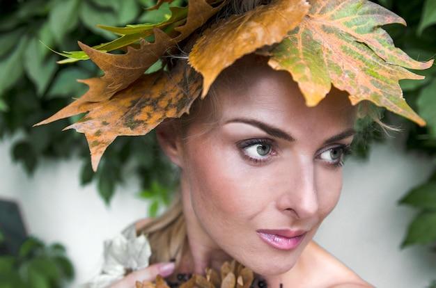 Jesieni dziewczyna z suchym liścia włosy styl. młoda kobieta z spadkiem opuszcza na głowie, zamyka up