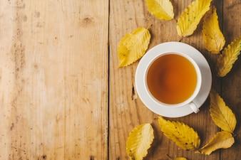Jesieni herbata na drewnianym stole z liśćmi