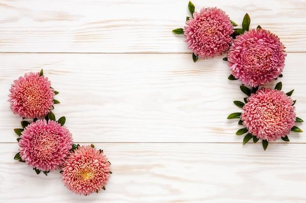 Jesieni kwiecisty tło - różowi astery na białym drewnianym stole.
