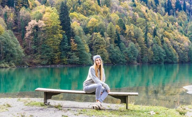 Jesieni ładna dziewczyna pozuje blisko halnego jeziora. jesień krajobraz w lesie.