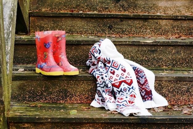 Jesieni owoc na rocznika starym drewnianym schody. jesienny nastrój, ciepłe ubrania. styl życia. ganek starego domu. czerwone kalosze.