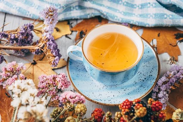Jesieni rozgrzewająca herbata na drewnianym stole z jesień drzewnymi liśćmi kłama w pobliżu