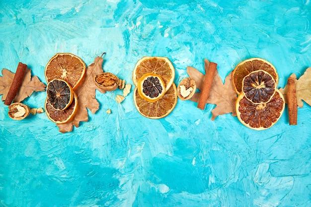 Jesieni składu tło z plasterkami wysuszone pomarańcze, liście i cynamon.